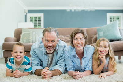 Portrait of smiling family lying together on carpet in living room
