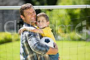 Father and son with football in the park on a sunny day