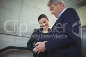 Businesspeople discussing over electronic device in corridor