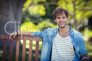Smiling man sitting on bench in park