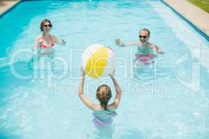 Happy parents and daughter playing with swim ball in swimming pool