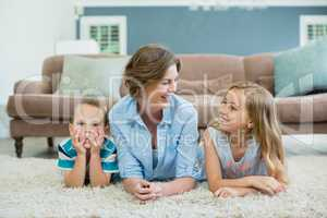 Smiling mother with her son and daughter lying on carpet in living room