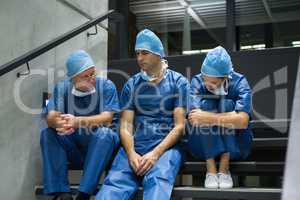 Group of worried surgeons sitting together on staircase
