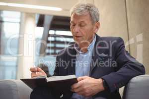 Attentive businessman writing in organizer