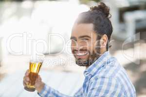 Man holding beer glass in the park on a sunny day