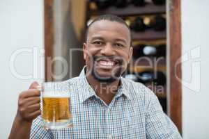 Handsome man smiling while holding beer glass