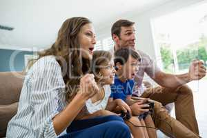 Excited family playing video games together in living room