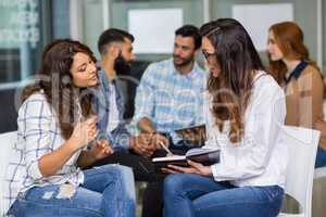 Female executives interacting with each other during meeting