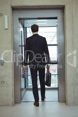 Rear view of businessman walking into an elevator