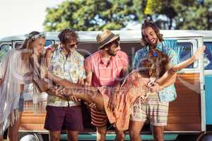 Group of friends lifting woman near campervan