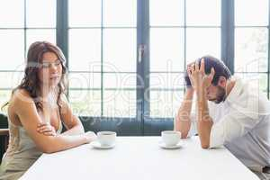 Depressed couple sitting with coffee cup