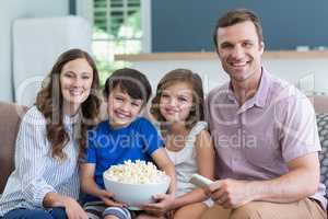 Smiling family watching tv and eating popcorn in living room at home