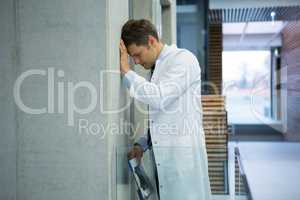 Worried male doctor leaning on wall near corridor