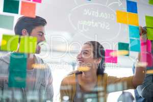 Smiling executives interacting with each other while writing on sticky notes on glass wall