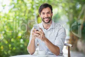 Man smiling while using his mobile phone n the restaurant