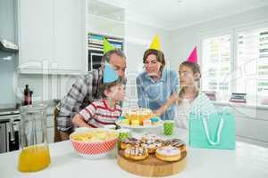 Family celebrating their sons birthday in kitchen