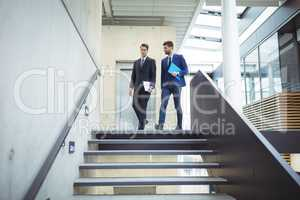 Two businessman walking down the stairs