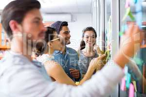 Smiling executives writing on sticky notes on glass wall