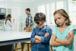 Sad siblings standing with arms crossed while parents arguing in background