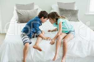 Angry brother and sister face to face on bed in bedroom