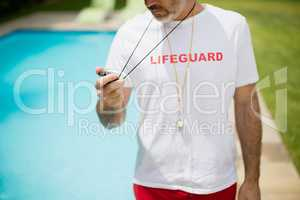 Swim coach looking at stop watch near poolside on a sunny day