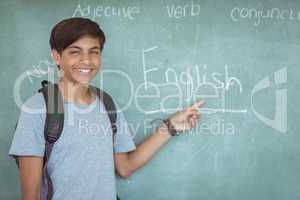 Portrait of happy schoolboy pointing at chalkboard in classroom