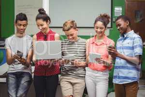 Students using laptop, mobile phone, digital tablet