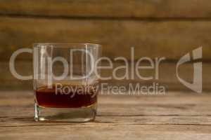 Glass of whisky on wooden table
