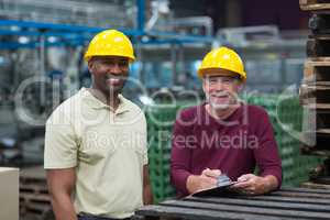 Two factory workers standing with clipboard in drinks production plant