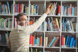 Portrait of happy school teacher selecting book in library