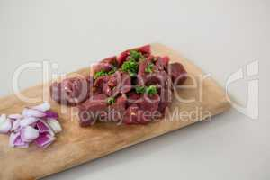 Minced beef and chopped onions on wooden tray