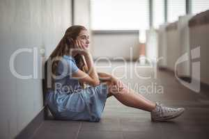 Sad schoolgirl sitting in corridor