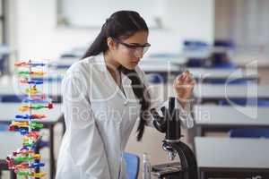 Attentive schoolgirl experimenting microscope slide in laboratory