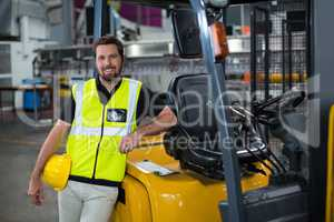 Portrait of smiling factory worker leaning on forklift