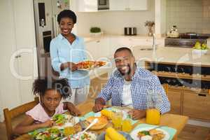 Portrait of happy woman serving food to the family