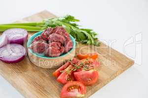 Minced beef and ingredients on wooden tray