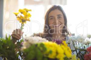Smiling woman holding a bunch of flowers at florist shop