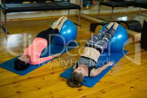 Determined women exercising with fitness ball