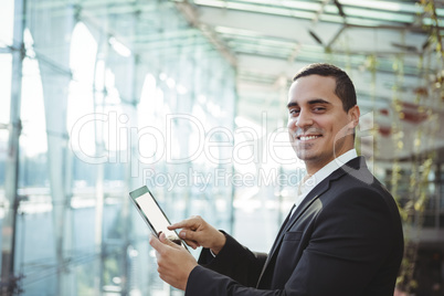 Smiling business executive using digital tablet at railway station