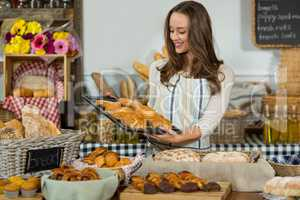 Smiling female staff holding tray of breads at counter