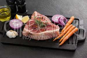 Sirloin chop and ingredients on black grill