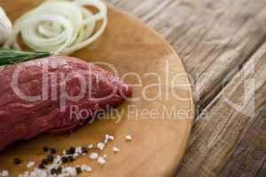 Beef steak, salt and onions on wooden tray against wooden background