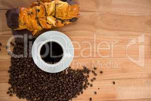 Coffee with roasted coffee beans and croissant