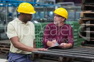 Factory workers discussing with a clipboard in drinks production plant