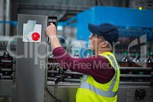 Factory worker operating machine