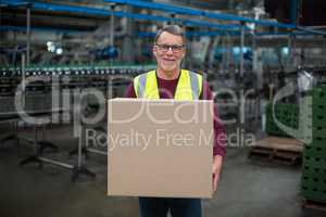 Portrait of factory worker holding cardboard box