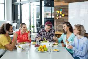 Smiling business executives having meal in office
