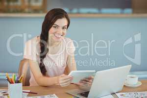 Portrait of beautiful business executive sitting at desk and using digital tablet