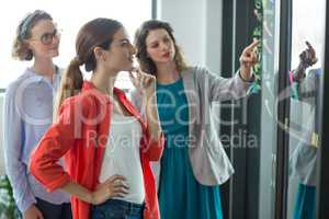 Business executives discussing over sticky notes on glass