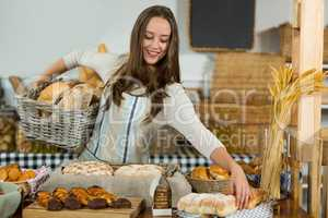Smiling female staff putting bread in basket at counter